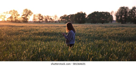 Young woman standing in the fields, centered in the image, holding the mobile phone and looking at it. Lonely young woman in the sunset in the field, looking at the screen of a mobile device.