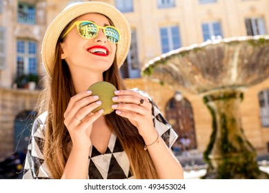 Young woman standing with french sweet cookie macaron on the square with fountain in the old town of Aix-en-Provence in France. Tourist having a great vacation in Provence