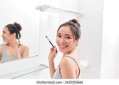 A young woman is standing in front of the bathroom mirror and putting on makeup.