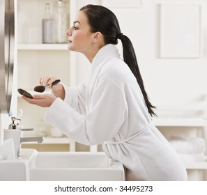 A young woman is standing in front of the bathroom mirror and putting on makeup.  Horizontally framed shot.