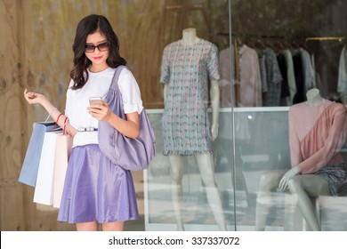Young woman standing in front of clothing store and reading text message