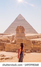 Young woman standing in front of the Great Sphinx of Giza With Khufu pyramid at the back. Valley of the Kings, Cairo, Egypt.