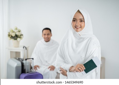 young woman standing in front of her husband wearing white traditional clothes for Ihram ready for Hajj