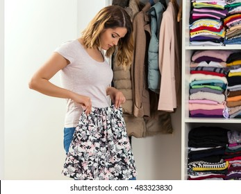 Young woman is standing in front of her closet and trying to find perfect outfit. She is not satisfied with the skirt she chose.
