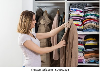 Young woman is standing in front of her closet trying to find perfect outfit.