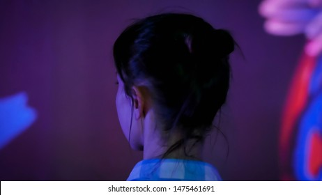 Young woman standing in front of interactive display and looking around at modern immersive exhibition with low light illumination. Education, digital art, technology and entertainment concept
