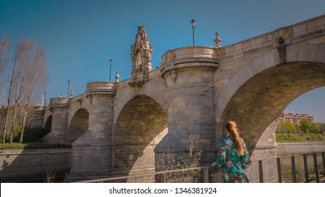 A young woman is standing in front of the medieval Toledo old limestone bridge or Puente de Toledo downtown Madrid, Spain at Madrid Rio across the Manzanares river on a warm spring day.