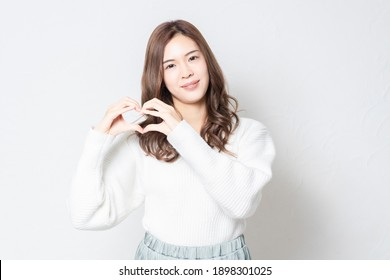 A young woman standing in front of a white wall and making a heart shape by hand, shot in the studio