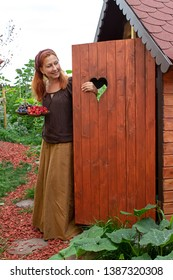 Young woman is standing with a fruit bowl at her garden shed