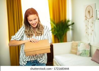 junge Frau, die in ihrer Wohnung steht und einen Karton in Händen hält, ein neues Paket erhält, online einkaufen geht oder einige Waren direkt von zu Hause an den Kunden schickt
