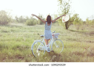 Young woman is standing with her back. She leaned on her bicycle and held up her hands.