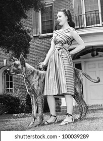 Young woman standing with her Great Dane in a courtyard