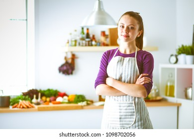 Young woman standing in her kitchen near desk . Young woman at kitchen