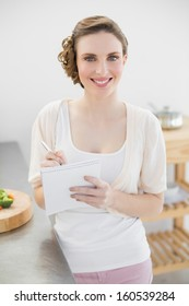 Young woman standing in her kitchen writing a shopping list smiling at camera at home