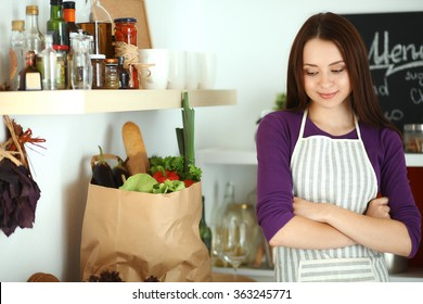 Young woman standing in her kitchen near desk with shopping bags
