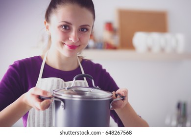 Young woman standing in her kitchen near desk