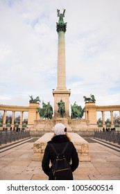 Young woman is standing in Heroes square and observing the monument in BudaPest, Hungary.