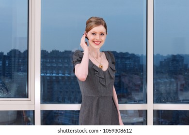 Young woman standing inside interior with large glass wall with urban view and wearing hedset in her ear