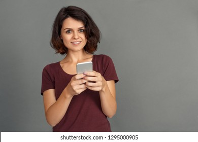 Young woman standing isolated on grey wall playing online game on smartphone looking camera smiling excited