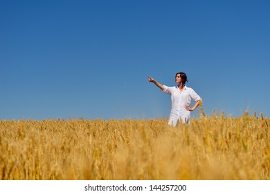 Young woman standing jumping and running  on a wheat field with blue sky the background at summer day representing healthy life and agriculture concept