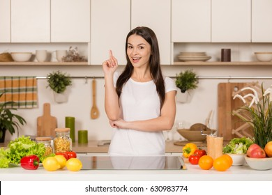 Young Woman standing in kitchen having idea and looking recipes in the kitchen. Side view