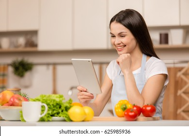 Young Woman standing in kitchen with tablet computer and looking recipes. Food blogger concept