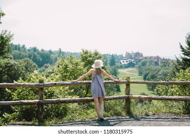 Young woman standing and looking at the mountains and forests