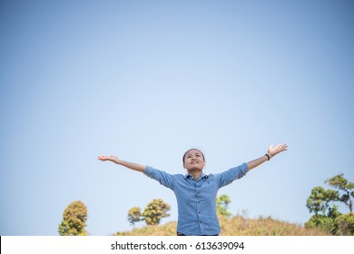 Young woman standing looking to a sky with raised hands while during hike in the mountain.