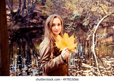 Young woman  standing with maple leaves in the hands. Girl walking in the forest and enjoying sunny weather. Lifestyle, autumn concept and relax.