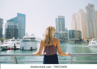 Young woman standing in Marina Walk Dubai and looking at the city