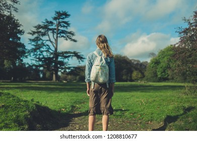 A young woman is standing in a meadow and is looking at a tree