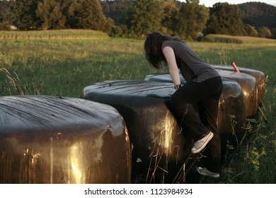 young woman standing in a meadow on bales of hay wrapped in black polyvinyl