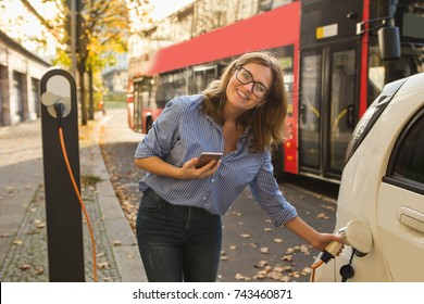 Young woman is standing near the electric car and looking at camera. The rental car is charging at the charging station for electric vehicles. Car sharing
