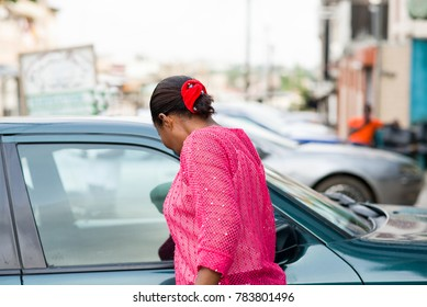 young woman standing near her car and looking inside through the window.