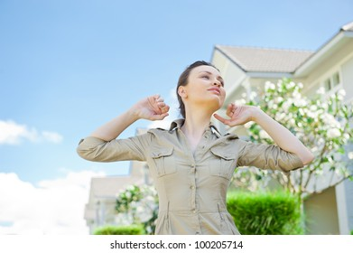 Young woman standing near house of her dream