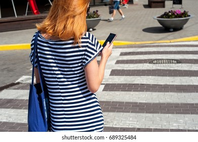 young woman standing near the pedestrian crossing