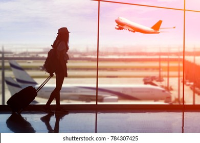 Young woman is standing near window at the airport and watching plane before departure. She is standing and carrying luggage.Travel Concept .