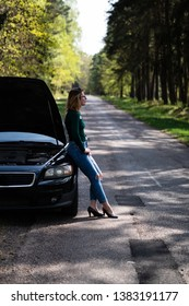 Young woman standing next to a broken car. Despaired young woman. Woman's car broken on countryside.
