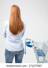 A young woman standing next to an empty shopping cart with her back toward the camera.