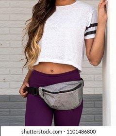 Young Woman Standing Next to a White Wall in Sportswear and a Fanny Pack