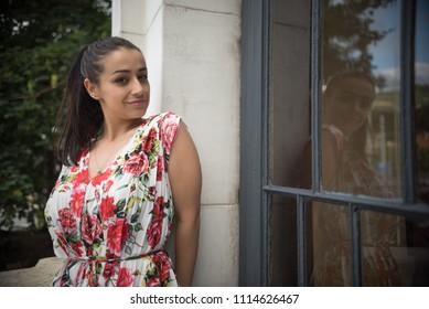 young woman standing on balcony near window
