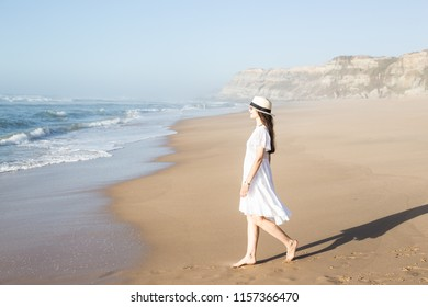 Young woman standing on the beach at the atlantic coast looking at the sea in Portugal