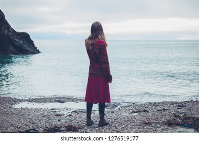 A young woman is standing on the beach looking at the sea