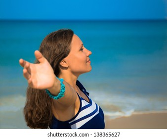 The young woman standing on a beach and looking afar with raised hands