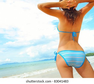Young woman standing on a beach and looking to the horizon.