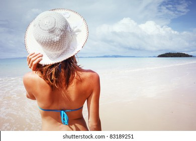 Young woman standing on a beach holding her straw hat and looking to the horizon.