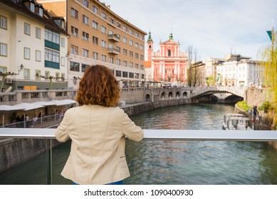 Young woman is standing on a bridge above Ljubljanica river looking at the Franciscan Church of the Annunciation and buildings on the riverbanks in Ljubljana, Slovenia.