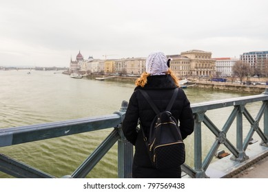 Young woman is standing on the Chain Bridge looking at the Hungarian Parliament Building in Budapest, Hungary