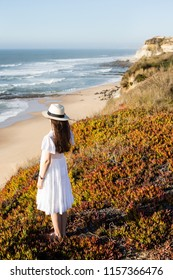 Young woman standing on the cliff at the atlantic coast looking at the sea in Portugal