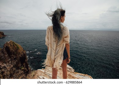 Young woman standing on cliff's edge and looking into a wide sea view. Wind Long dyed hair hairstyle. View from the back.